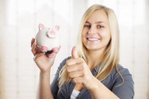 Anwaltskosten. Blonde Frau mit Sparschwein in der Hand zeigt Daumen hoch